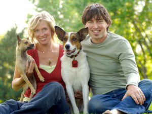 man and woman holding two dogs